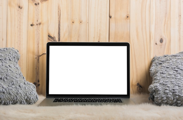 Laptop and pillow on soft fur against wooden background Free Photo