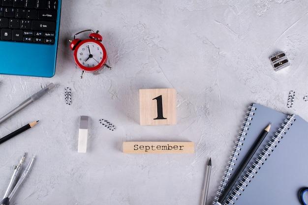 Ноутбук, красный будильник и принадлежности, деревянный календарь Premium Фотографии