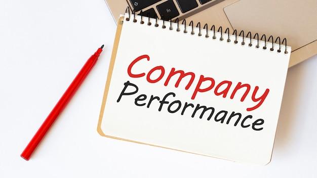 ノートパソコン、赤ペン、テキスト付きメモ帳会社のパフォーマンス Premium写真