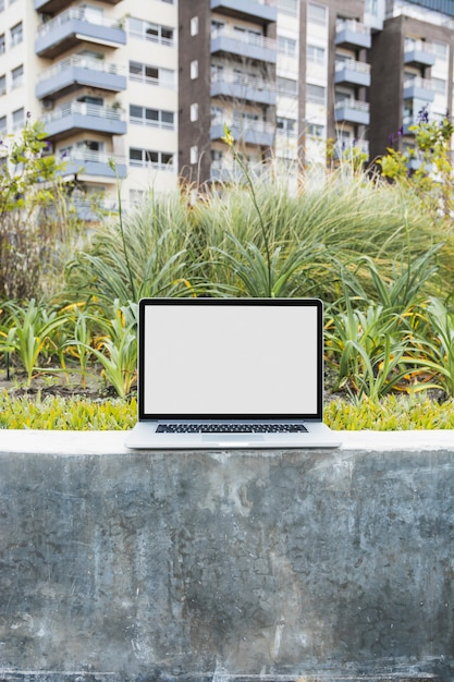 Laptop on retaining wall in front of apartment Free Photo