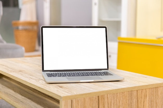 Laptop showing blank screen on work table front view in home Premium Photo