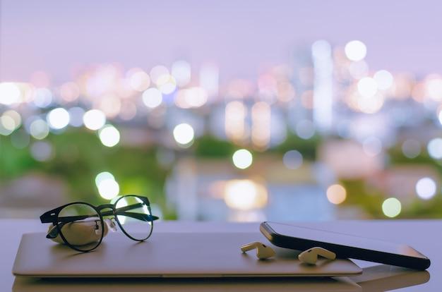 Отключение ноутбука, смартфона и наушников положить на стол с красочными огни города боке. Premium Фотографии