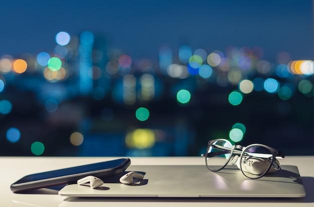 Ноутбук, смартфон и наушники выключаются, положить на стол с красочными городскими огнями боке Premium Фотографии