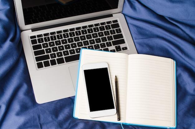 아침 시간에 침대에 노트북, 스마트 폰 및 노트북. 모의 프리미엄 사진