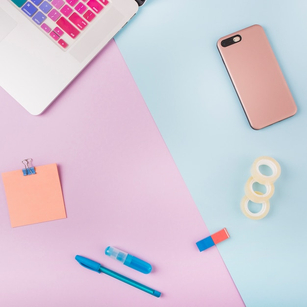 Laptop; smartphone; cello tape and adhesive note on colorful cardboard papers Free Photo