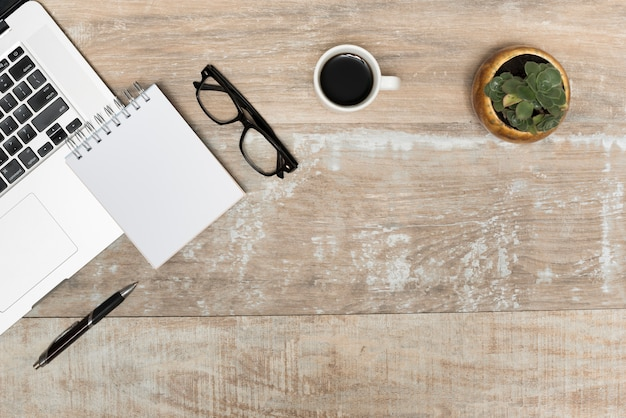Laptop; spiral notepad; eye glasses; black tea and plant on wooden table Free Photo