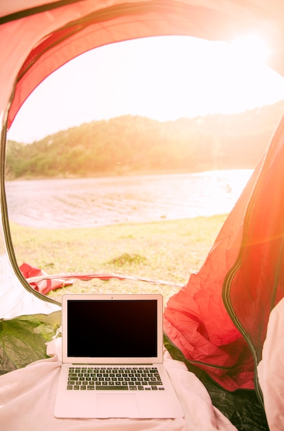 Laptop standing in tent outdoors Free Photo