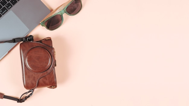 Laptop; sunglasses and camera in its case on plain colored background Free Photo
