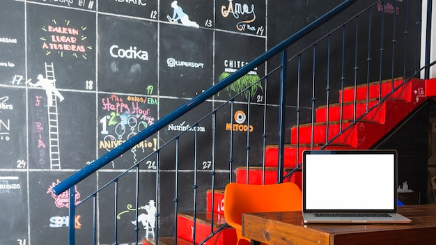 Laptop on table in front of staircase and decorative wall Free Photo