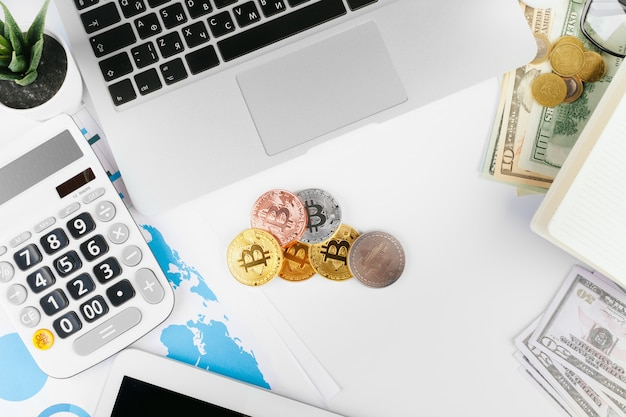 Laptop on the table near dollars and bitcoins in the office Premium Photo