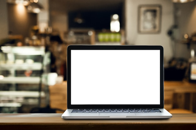 Laptop on the table with coffee shop background. Premium Photo
