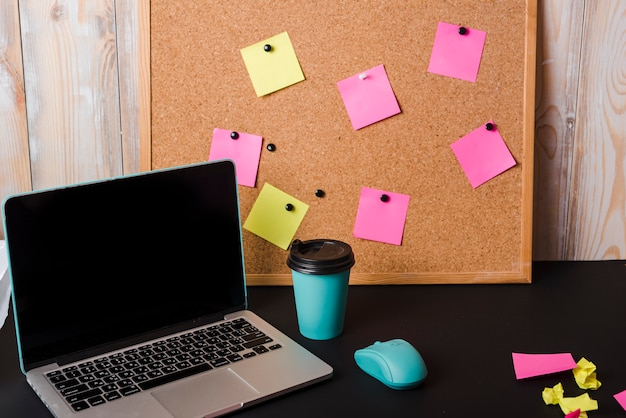 Laptop; takeaway coffee cup; mouse and corkboard with adhesive notes on black desk Free Photo