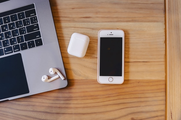 A laptop, a telephone and a wireless headset on a wooden table Premium Photo