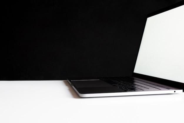 Computer portatile in cima a un tavolo da lavoro in nero Foto Gratuite