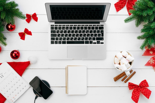 Laptop on white wooden desk surrounded with red christmas decorations, top view Premium Photo