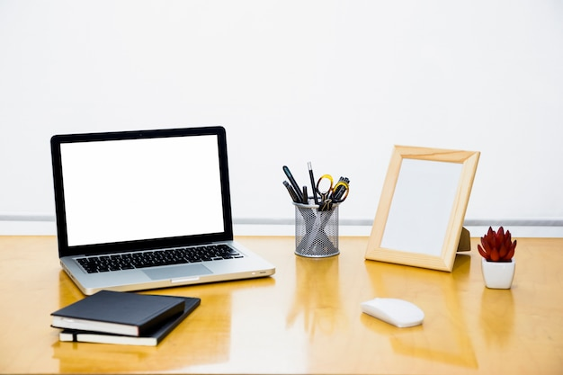 Laptop with blank frame on wooden table Free Photo