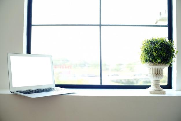 Ноутбук с пустой экран на деревянный стол перед окном. Premium Фотографии