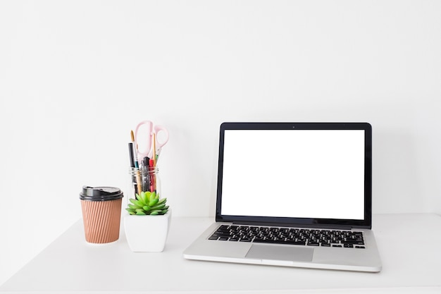 Laptop with blank white screen and disposal cup on desk Free Photo