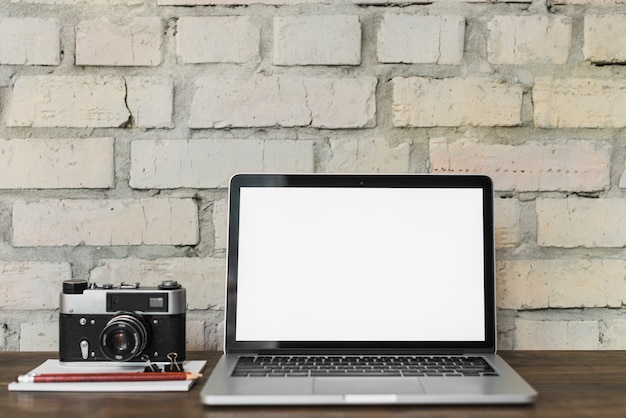 Laptop with blank white screen near camera; notepad; pencil and bulldog clip on wooden desk Free Photo