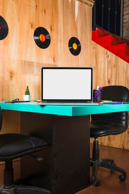 Ноутбук с пустой белый экран на деревянный стол в офисе Бесплатные Фотографии