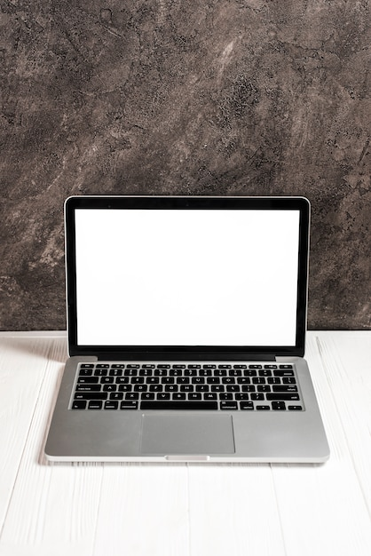 Laptop with blank white screen on white wooden table against concrete Free Photo