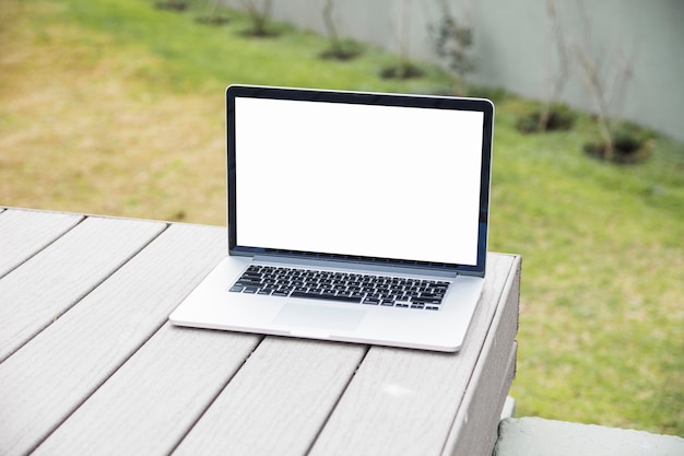 Laptop with blank white screen on wooden desk Free Photo