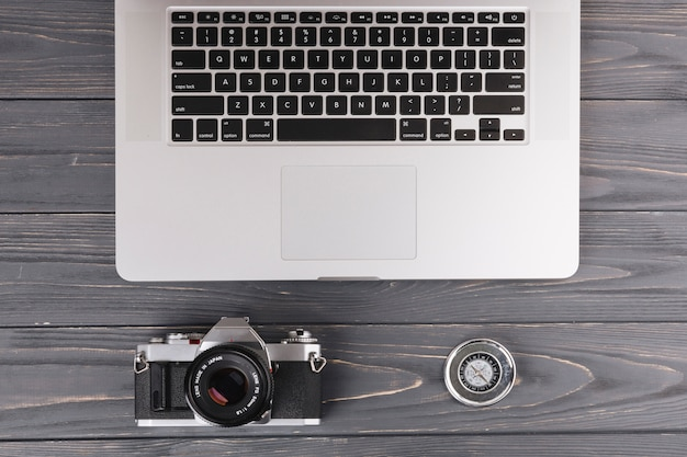 Laptop with camera and compass on wooden table Free Photo