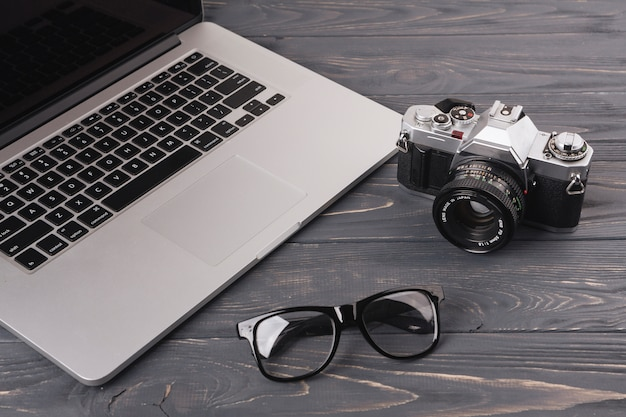 Laptop with camera and glasses on table Free Photo