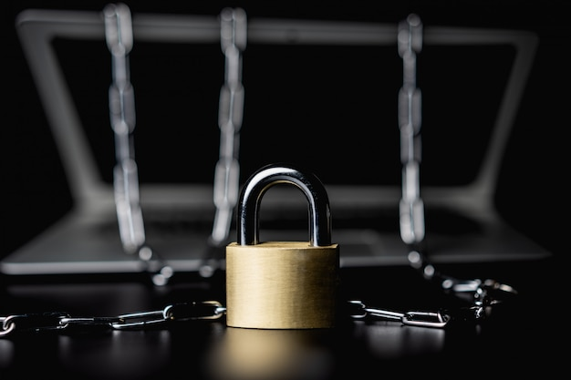 Laptop with chains and lock on black isolated Premium Photo