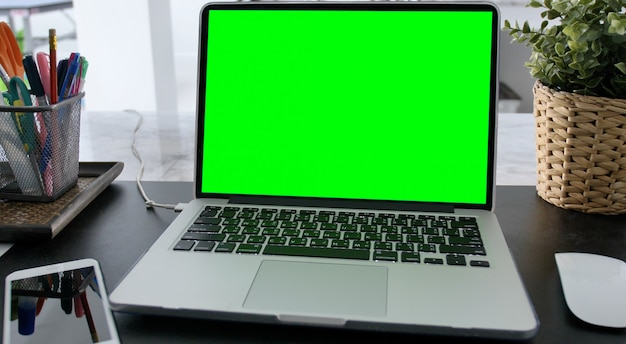 Laptop with green screen for replacement with blur background Premium Photo