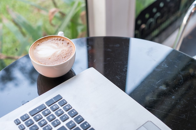 Laptop with latte hot coffee in white cup on glass table Premium Photo