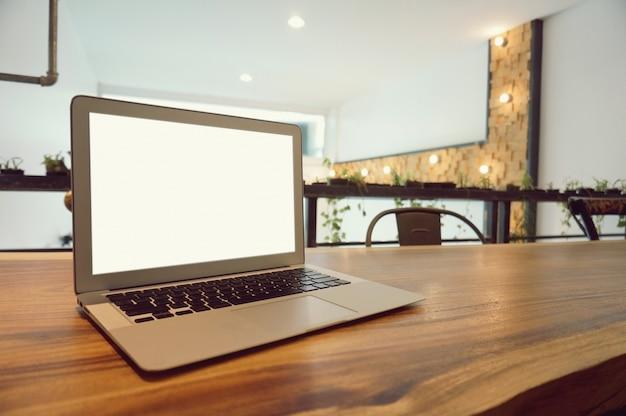 Ноутбук с макет пустой экран на деревянный стол в передней части coffeeshop кафе место для текста. концепция дисплея дисплея продукта Premium Фотографии