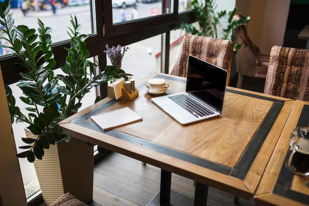 Laptop with notepad in cafe on table Free Photo