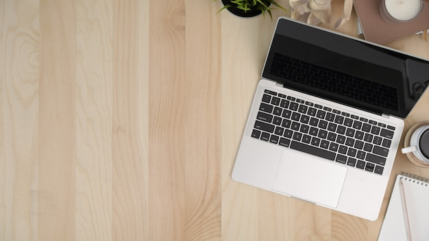 Laptop with office accessories on wooden workspace table and copy space Premium Photo