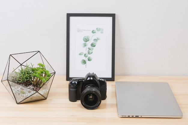 Laptop with picture and camera on wooden table Free Photo