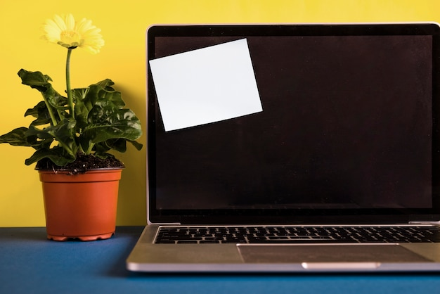 Laptop with post-it note on opened lid Free Photo