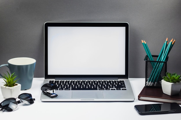 Laptop with smartphone on table Free Photo