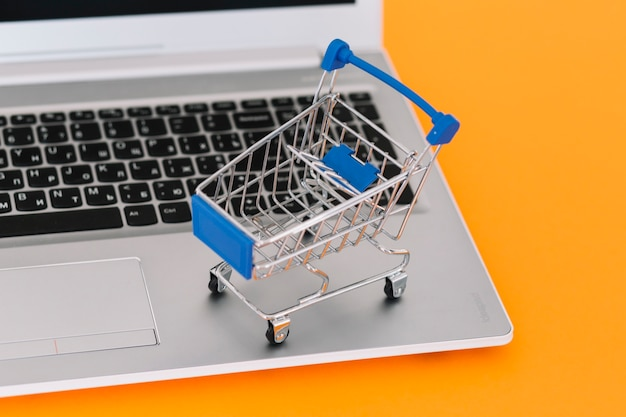 Laptop with toy shopping trolley  Free Photo