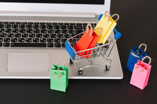Laptop with toy supermarket cart and packages Premium Photo