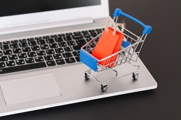 Laptop with toy supermarket cart and packet Free Photo