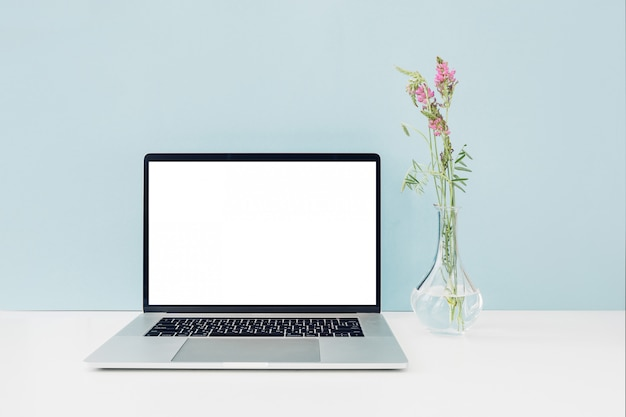 Laptop with white blank screen and flowers in vase on table on blue. mock up Premium Photo