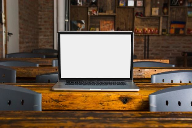 Laptop with white display screen on wooden table in the caf� Free Photo
