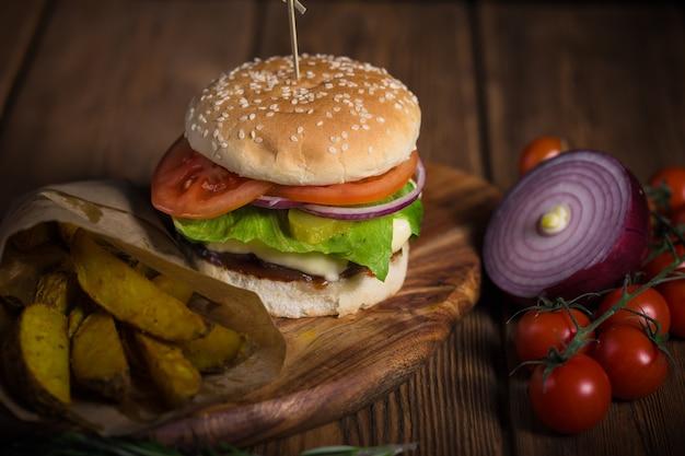 木製の表面に牛肉、ジャガイモ、チーズの食欲をそそる大きなハンバーガー Premium写真