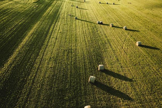Grande bellissimo campo agricolo con pile di fieno sparato dall'alto Foto Gratuite