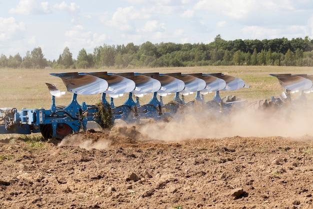 큰 파란색 쟁기는 밭의 토양을 쟁기질하고 건조한 토양의 많은 먼지가 쟁기에서 날아갑니다. 프리미엄 사진
