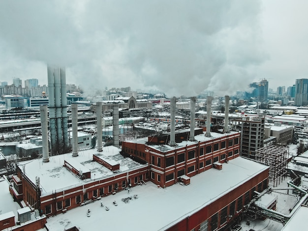 Large central boiler room with giant pipes of which there is dangerous smoke in winter during frost in a big city Free Photo