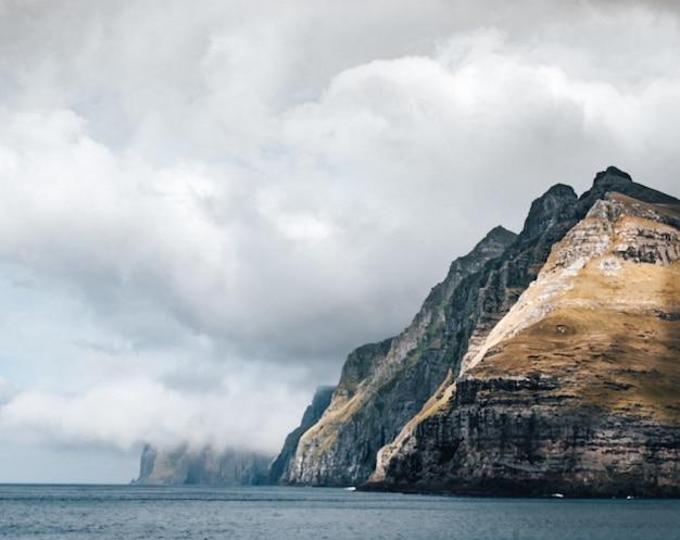 雲の下の水に囲まれた大きな崖 無料写真