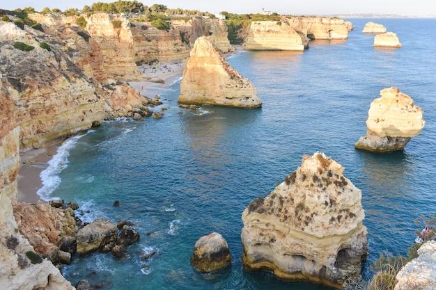 Большие скалы, торчащие из воды днем Бесплатные Фотографии