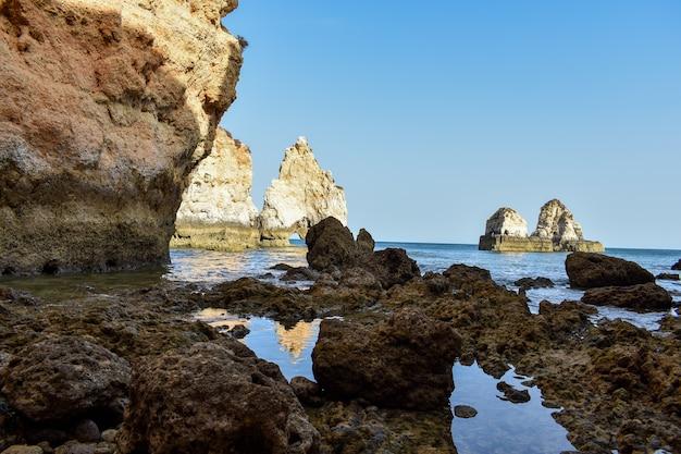 Grandi scogliere sporgenti dall'acqua durante il giorno a lagos, portogallo Foto Gratuite