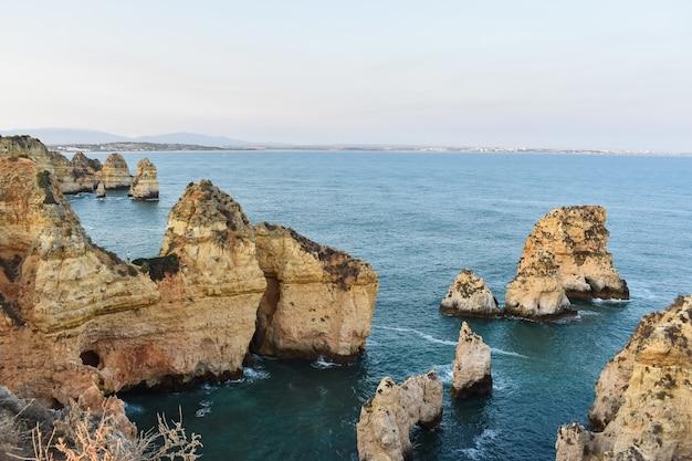 Grandi scogliere che fuoriescono dall'acqua durante il giorno in portogallo Foto Gratuite